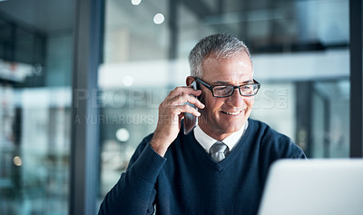 Buy stock photo Shot of a mature businessman using a cellphone and laptop while working late in an office