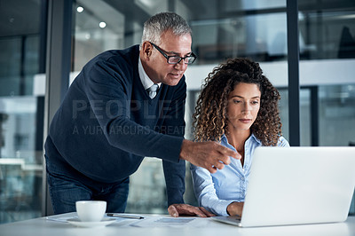 Buy stock photo Shot of two businesspeople working late on a laptop in an office