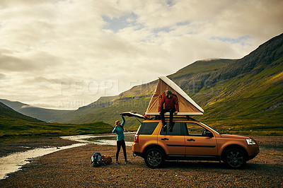 Buy stock photo Shot of two cheerful young hikers setting up a tent on top of their car outside in a rural area