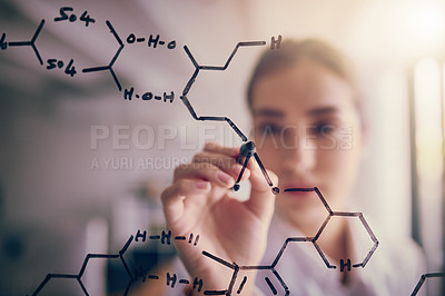 Buy stock photo Shot of a focused young female scientist solving equations on a glass wall in a laboratory