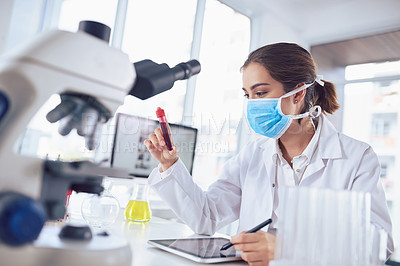 Buy stock photo Shot of a focused young female scientist wearing a surgical mask and holding a vile of blood inside a laboratory