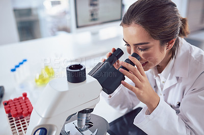 Buy stock photo Shot of a cheerful young female scientist looking through the lens of a microscope while being seated inside of a laboratory