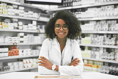 Buy stock photo Portrait of a cheerful young female pharmacist standing with arms folded while looking at the camera in a pharmacy
