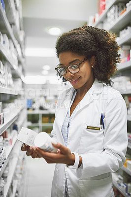 Buy stock photo Shot of a cheerful young female pharmacist holding two different types of medication in each hand in a pharmacy