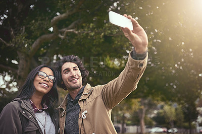 Buy stock photo Shot of a cheerful young couple taking a self portrait together while standing outside in a park