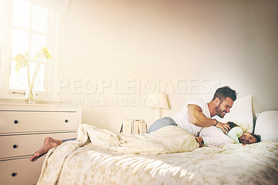 Buy stock photo Shot of a cheerful father and daughter having a tickle fight on the bed at home