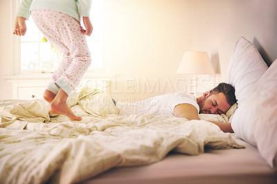 Buy stock photo Shot of a cheerful little girl jumping on the bed to wakeup her sleeping dad at home