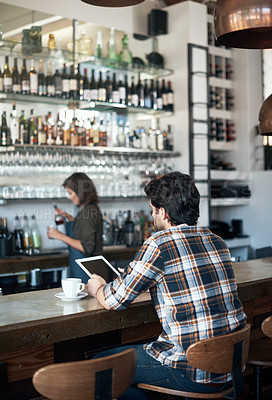 Buy stock photo Rearview shot of a unrecognizable young man working on a digital tablet while being seated at a bar