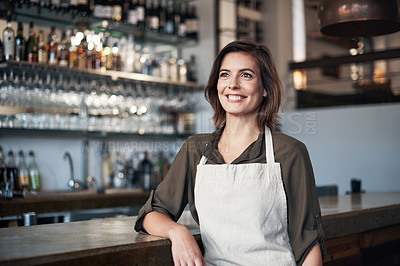 Buy stock photo Shot cheerful female bartender standing in front of the bar counter while leaning on it and looking into a certain direction