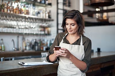 Buy stock photo Shot of a cheerful young female bartender busy texting on her cellphone while standing next to the bar counter