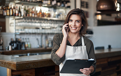 Buy stock photo Portrait of a cheerful young female bartender making a call while looking at the camera inside of a restaurant
