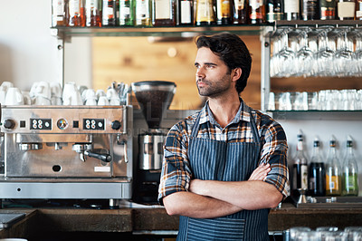 Buy stock photo Shot of a cheerful young male bartender standing with arms folded inside of a restaurant