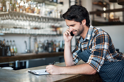Buy stock photo Shot of a cheerful young male bartender making a call and contemplating while standing inside of a restaurant