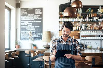 Buy stock photo Shot of a focused young male bartender making notes in a book while standing next to a bar counter