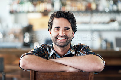 Buy stock photo Portrait of a cheerful young man sitting with his arms folded while looking at the camera inside of a