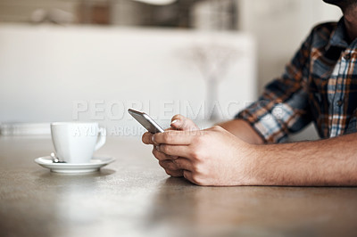 Buy stock photo Closeup of a unrecognizable man texting on his phone while being seated at a table
