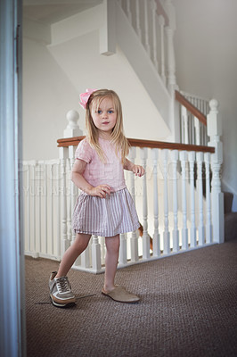 Buy stock photo Shot of an adorable little girl walking around the house in grown up shoes