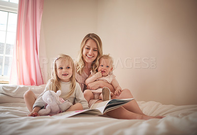 Buy stock photo Shot of an adorable family of three reading a book together on the bed at home