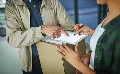Buy stock photo Cropped shot of a woman using a digital tablet to sign for a package from a delivery man