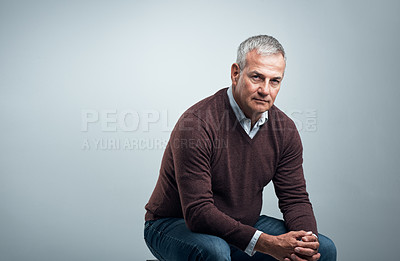 Buy stock photo Studio shot of a handsome mature man sitting on a chair against a grey background