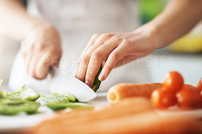Buy stock photo Closeup shot of a young woman chopping vegetables in the kitchen