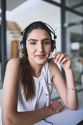 Buy stock photo Portrait of a cheerful businesswoman talking to a customer using a headset while looking at the camera
