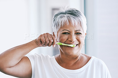 Buy stock photo Portrait of a cheerful mature woman brushing her teeth while looking at the camera at home