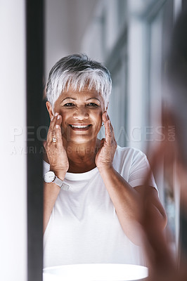 Buy stock photo Shot of a cheerful mature woman touching her face with her hands while looking at her reflection in a mirror