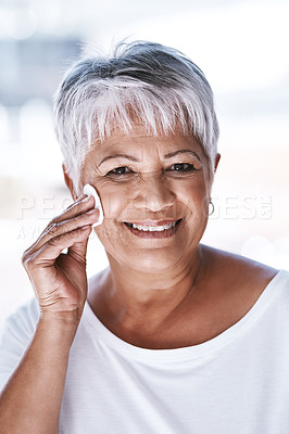 Buy stock photo Portrait of a cheerful mature woman applying makeup remover on her face while looking at the camera