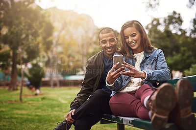 Buy stock photo Shot of a cheerful young couple sitting down on a bench while using a phone together outside in a park