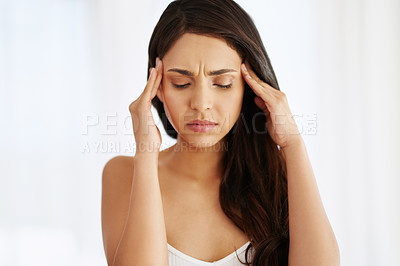 Buy stock photo Shot of a young woman experiencing stress at home
