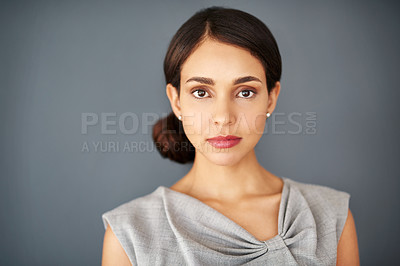 Buy stock photo Studio portrait of an attractive young businesswoman posing against a gray background