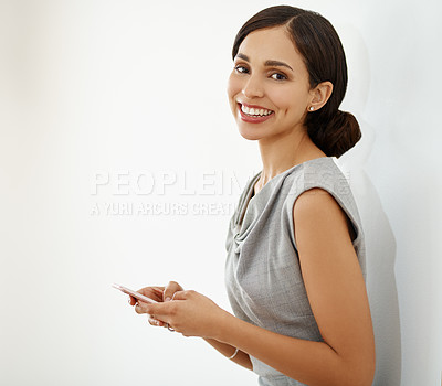 Buy stock photo Portrait of an attractive young businesswoman leaning against a wall and using a mobile phone