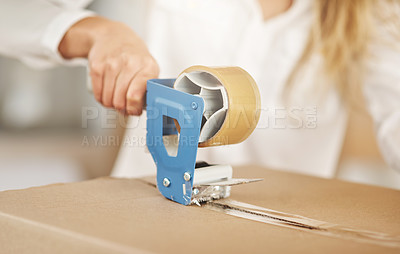 Buy stock photo Closeup shot of an unrecognizable woman sealing a box on moving day
