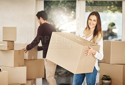 Buy stock photo Portrait of an attractive young woman carrying a box with her husbands in the background