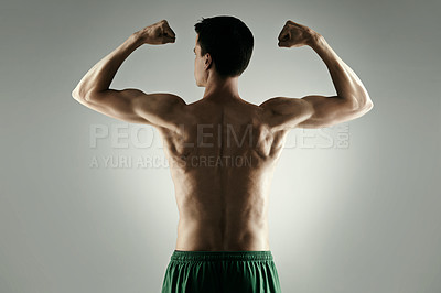 Buy stock photo Studio shot of an athletic young sportsman flexing against a grey background