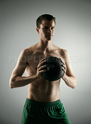 Buy stock photo Studio shot of a shirtless young male athlete working out with a medicine ball against a grey background