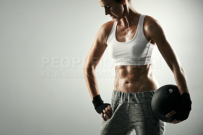 Buy stock photo Studio shot of an athletic young woman working out with a medicine ball against a grey background