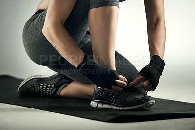 Buy stock photo Studio shot of an unrecognizable young sportswoman tying her laces while working out on an exercise mat against a grey background