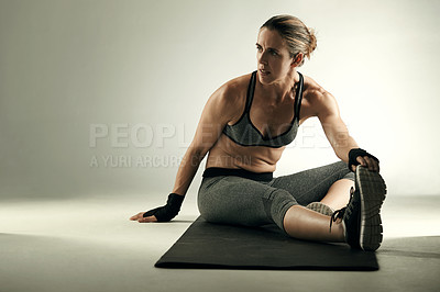Buy stock photo Studio shot of an athletic young sportswoman working out on an exercise mat against a grey background