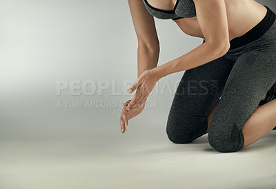 Buy stock photo Studio shot of an unrecognizable young sportswoman working out against a grey background