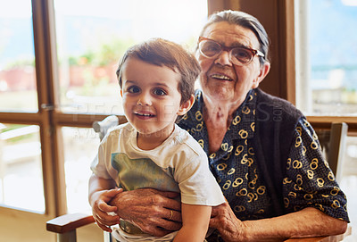 Buy stock photo Portrait of a cheerful little boy sitting on his great grandmother's lap while looking into the camera at home