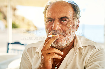 Buy stock photo Portrait of a confident senior man  smoking a cigarette and standing outside while looking at the camera