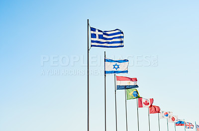 Buy stock photo Shot of a variety of different kinds of country's flags standing next to each other outside during the day