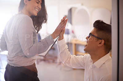 Buy stock photo Shot of two young businesspeople high fiving in an office