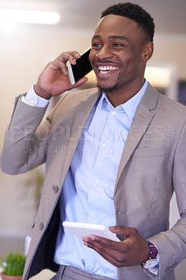 Buy stock photo Shot of a young businessman talking on a cellphone while using a digital tablet in an office