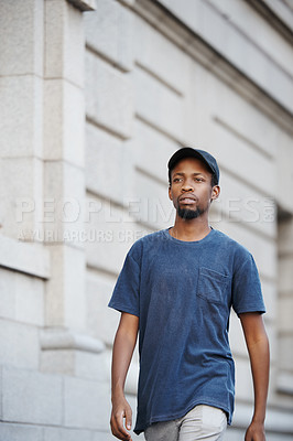 Buy stock photo Cropped shot of a handsome young man walking in the city
