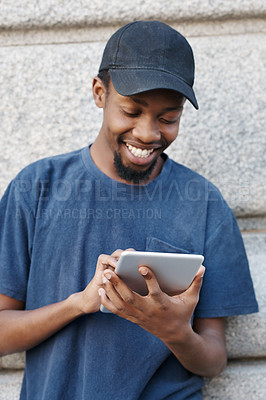 Buy stock photo Cropped shot of a young man using his digital tablet while out in the city