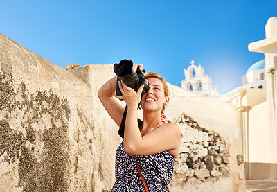 Buy stock photo Shot of a cheerful young woman taking photos of the area outside during the day