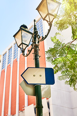 Buy stock photo Shot of a directional sign on a streetlamp outside during the day